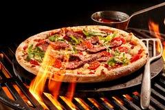 Flammor som når upp in mot pizza på galler Arkivfoto