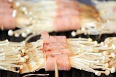 Flammulina Velutipes Mushrooms and bacon on grill. Royalty Free Stock Photos