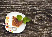 Flan creme caramel dessert. Flan - delicious creme dessert with caramel sauce.French creme caramel dessert or flan with strawberry and mint,  on the wooden Royalty Free Stock Image