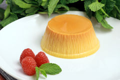 Flan dessert. Made with prime organic milk, berries and garnished with mint Stock Photography