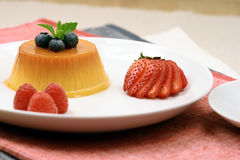 Flan dessert. Made with prime organic milk, berries and garnished with mint Stock Images