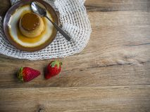 Flan in a plate. On wood background Stock Image