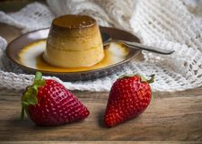 Flan in a plate. On wood background Stock Photo