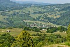 Flanc de coteau et village roumains Photos libres de droits