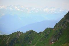 Flanc de coteau vert. montagnes avec des capuchons de neige photo stock