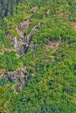 Flanc de montagne boisé avec des cascades Image stock