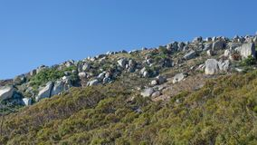Flank of hill. Stony flank of hill and blue sky stock photos