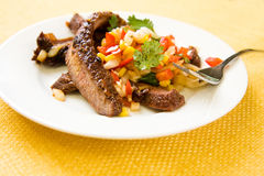 Flank steak. On white plate with corn salsa royalty free stock image
