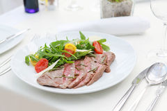Flank steak. á la Tagliata style, with arugula, cherry tomatoes served with Grana Padano cheese royalty free stock photos