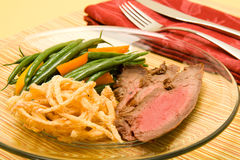 Flank steak. Sliced flank steak served with french green beans and crispy fried onions stock photo