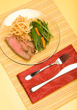 Flank steak. Sliced flank steak served with french green beans and crispy fried onions stock photography
