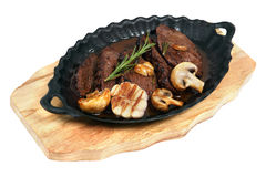 Flank steak baked in an oval cast iron plate. Flank Steak with mushrooms cooked in a cast iron dish oval, standing on a wooden board, studio shot, isolated on royalty free stock photos