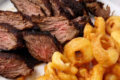 Flank steak with fries onion rings Royalty Free Stock Images