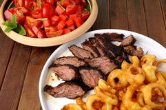 Flank steak with fries onion rings and salad Stock Photos