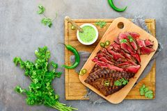 Flank steak on a wooden cutting board. Flank steak ready to eat cut and served on a wooden cutting board with chimichurri sauce, overhead view royalty free stock images