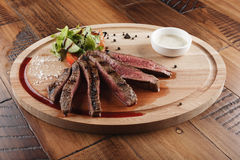 Flank steak. With salad and sauce on wooden surface stock photo