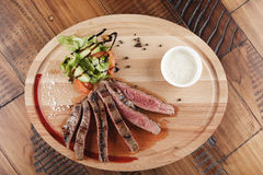 Flank steak with salad. And sauce on wooden surface Royalty Free Stock Image