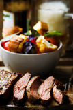 Flank steak  with tomato salad. Flank steak  with tomato salad and glass of beer. style vintage.  selective focus Stock Images