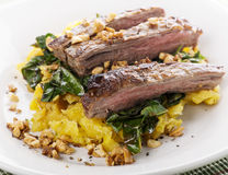 Flank steak with vegetables. Flank steak with mashed plantain , collard greens and ginger peanuts royalty free stock image