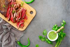 Flank steak on a wooden cutting board culinary background. Background with flank steak ready to eat cut and served on a wooden cutting board with chimichurri royalty free stock photos