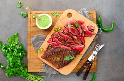 Flank steak on a wooden cutting board. Flank steak ready to eat cut and served on a wooden cutting board with chimichurri sauce, overhead view royalty free stock photos