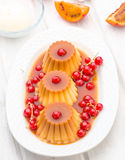 Flans with red currants and syrup in white tray Royalty Free Stock Photography