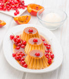 Flans with red currants and syrup in white tray Stock Photo
