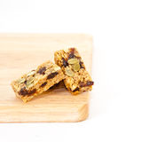 Flapjack. Pumpkin seed and raisin flapjack on a wooden chopping board, white background Stock Photo