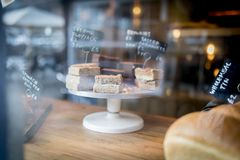 Flapjack and cake selection on a display on a cake stand in a bakery shop window. In the UK Royalty Free Stock Photography