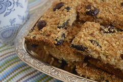Flapjack. Delicious bar with oatmeal, honey and dried fruit on silver platter Royalty Free Stock Images