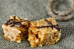 Flapjack. On a hessian background with chocolate sauce decoration Royalty Free Stock Photos