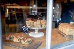 Flapjack- och kakavalet på en skärm på en kakaställning i ett bageri shoppar fönstret arkivbild