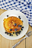 Flapjacks with blueberries and a fork on a board Stock Photo