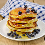 Flapjacks with blueberries and honey on the board Royalty Free Stock Images