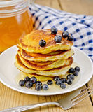 Flapjacks with blueberries and a jar of honey on the board Royalty Free Stock Image