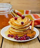 Flapjacks with cranberry and a jar of honey on the board Royalty Free Stock Photo