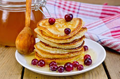 Flapjacks with cranberry and spoon on board Royalty Free Stock Images