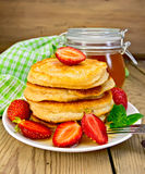 Flapjacks with strawberries and honey on board Royalty Free Stock Photos