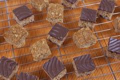 Flapjacks y mordeduras del caramelo del chocolate en un estante de enfriamiento Imagenes de archivo