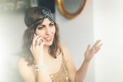Flapper girl talking on a smartphone Stock Image