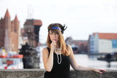 Flapper girl vintage woman in 1920s style Gdansk. Flapper girl. Retro styled fashion portrait of vintage woman from roaring 1920s outdoor. Old town Gdansk in the royalty free stock image