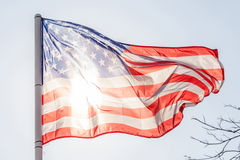 Flapping американского флага на небе с солнечным светом от задней части стоковые изображения rf