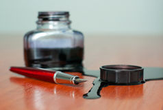 Flaque à l'encre noire près de crayon lecteur rouge sur la table Images libres de droits