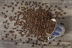 Flaque de tasse de café la table en bois de haricots un fond foncé Retrait bleu Photo stock