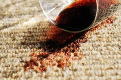 Flaque de vin rouge sur un tapis pur de laines Photo stock