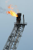 Flare boom nozzle and fire on offshore oil rig. Stock Images