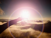 Flare. Lens defect, reflections.  Open hand with long fingers touch Sun.  Hilly landscape Stock Image