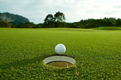 The flare lights photo of white golf ball near hole on fairway w royalty free stock photography