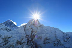 Flare over nuptse summit beside of everest Stock Photos