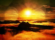 Autumn sunrise forest in a beautiful mountain within inversion. Treetops increased from fog Royalty Free Stock Photo